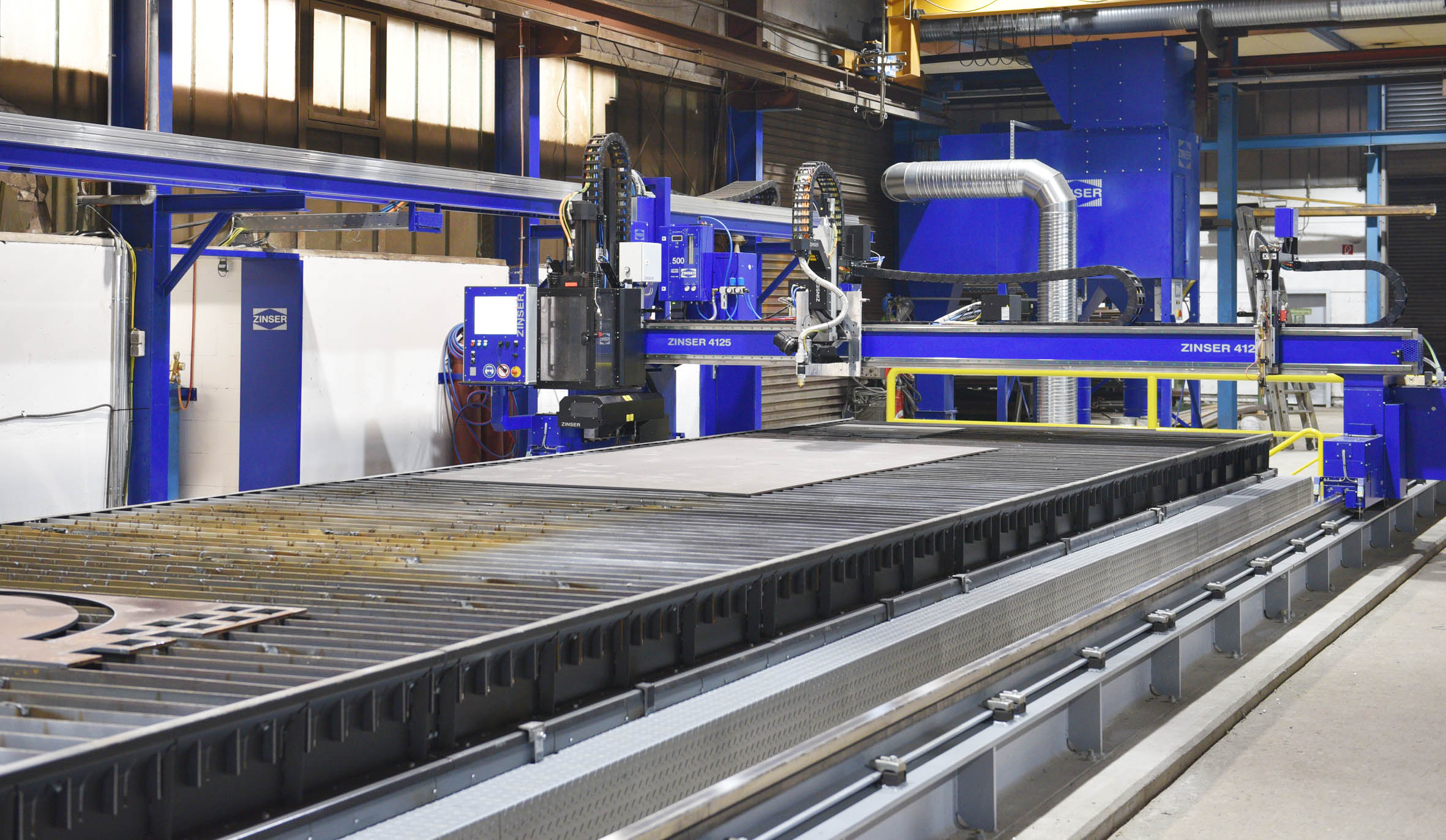 ZINSER 4125 CNC cutting machine with oxy-fuel torch, plasma torch and drilling unit over a ZINSER ZINtrac cutting table with oscillating conveyor