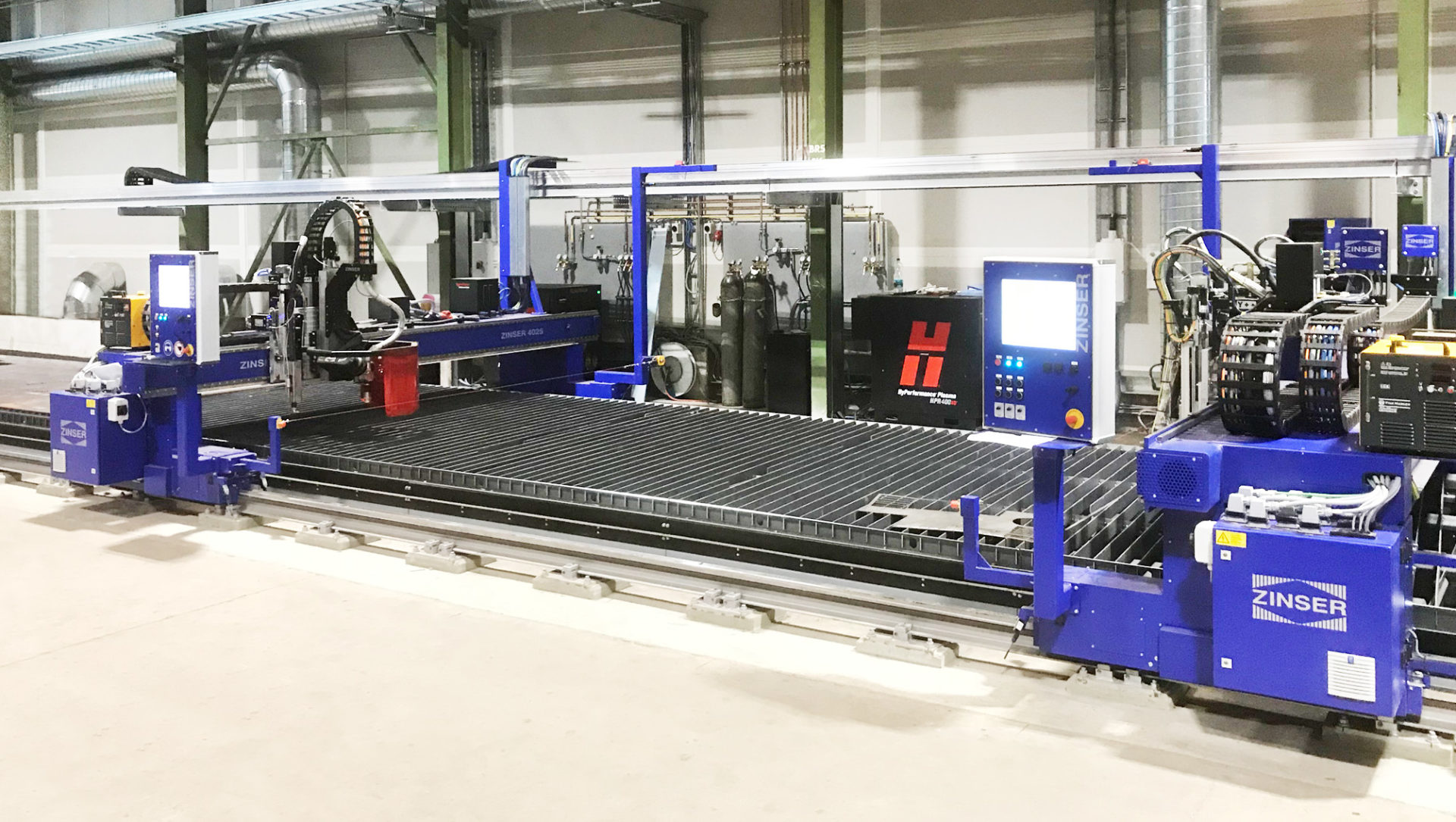 [:de] Zwei ZINSER Schneidmaschinen, ausgestattet mit einem Fasenaggregat, Autogen- und Plasmabrennern. [:en] Two ZINSER cutting machines equipped with a plasma bevel head, oxy-fuel and plasma torches